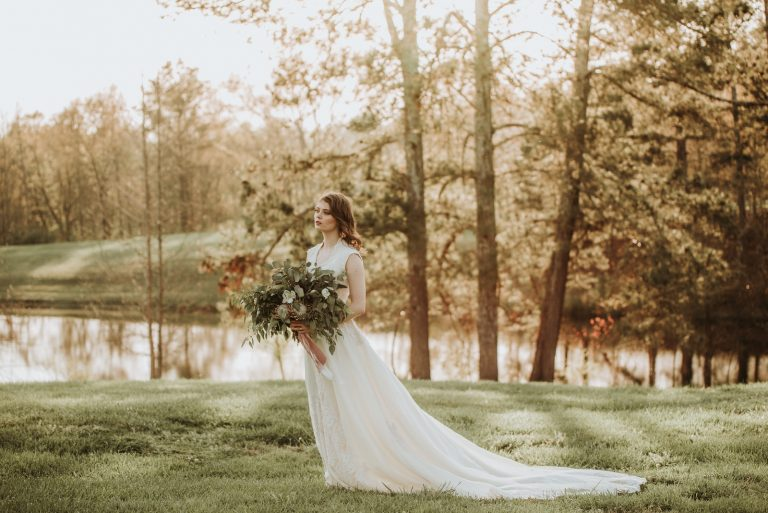 Bride with bouquet by lake