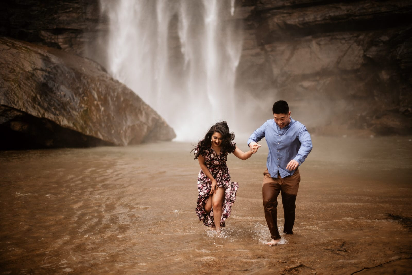 Couple running in water before Toccoa Falls