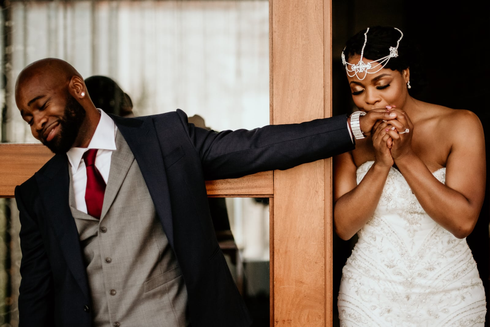 Bride delicately kissing the grooms hand prior to the first look