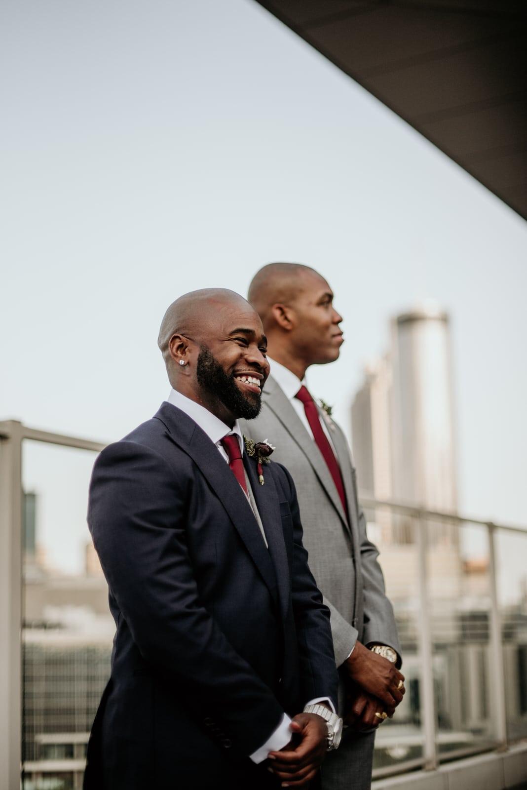 Groom smiling as he awaits his bride